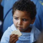 A migrant child eats emergency ration food on the Migrant Offshore Aid Station (MOAS) ship MV Phoenix after being rescued from an overloaded wooden boat 10.5 miles (16 km) off the coast of Libya August 6, 2015.  REUTERS/Darrin Zammit Lupi